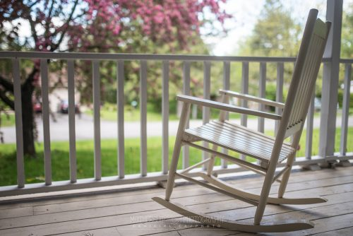 Photograph of a rocking chair on a porch