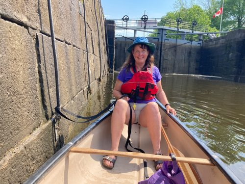 woman in a canoe in the midst of locking through the Rideau Canal